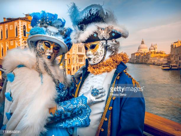 a couple of people in mask along the grand canal during the venice carnival - venice carnival stock pictures, royalty-free photos & images