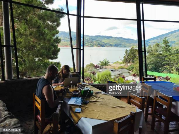 couple of people working on personal computers over breakfast on a conference in a rural location - cali colombia stock pictures, royalty-free photos & images