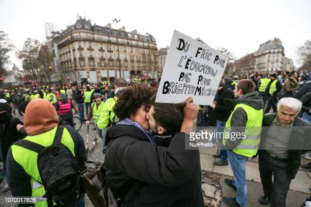 A couple of protestors making out hold a sign reading « Money for education not for Brigitte Macron » as they demonstrate against rising costs of...