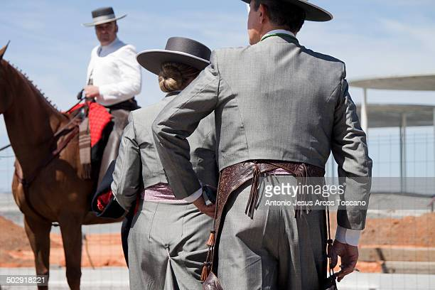 Couple of riders dressed in traditional flamenco dresses for riding, also a rider in the background is wearing a white jacket that are a hallmark of...