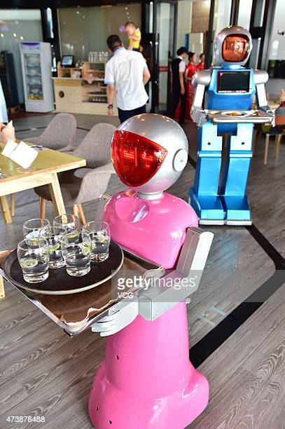 A couple of robot waiters deliver meals for customers at robotthemed restaurant on May 18 2015 in Yiwu Zhejiang province of China Sophomore Xu Jinjin...