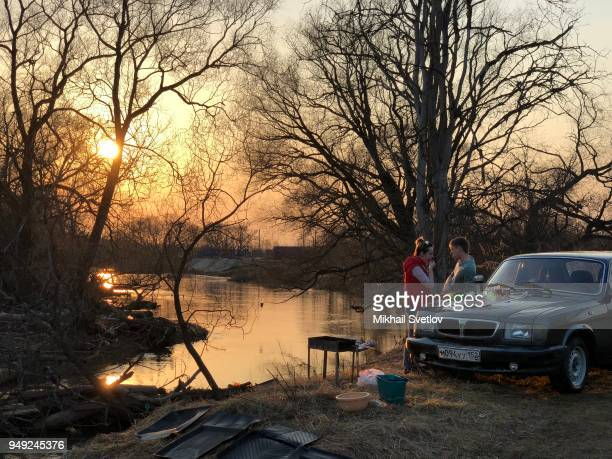 A couple of Russians cook and relax on the banks of Istra river near their Volga car in Zelenkovo villiage outside of Moscow Russia April 2018...