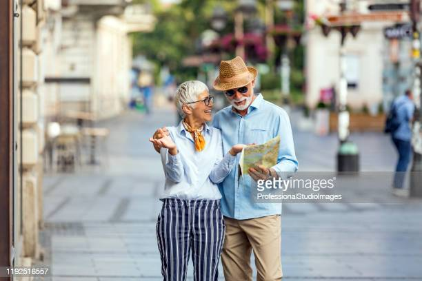 a couple of senior tourists exploring the city - studio city stock pictures, royalty-free photos & images