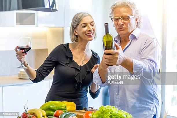 Couple of seniors tasting wine at home