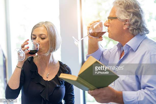 couple of seniors tasting wine at home - pjphoto69 stock pictures, royalty-free photos & images