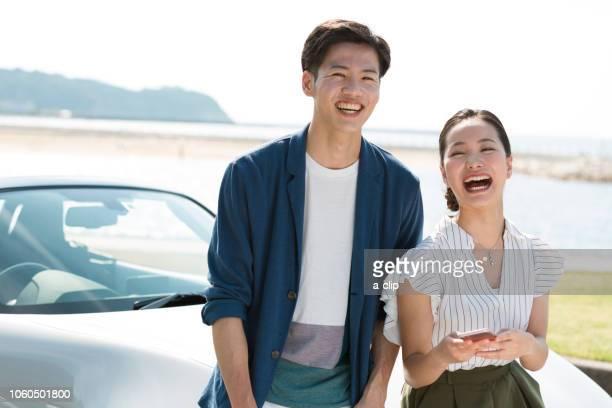 a couple of smiling faces in an open car - landfahrzeug stock-fotos und bilder