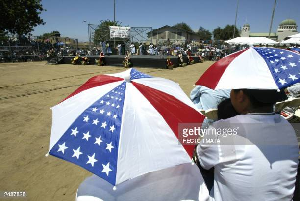 A couple of spectators wearing hats look at a traditional Oaxcan dance performance during the celebrations of the Guelaguetza in Los Angeles 03...