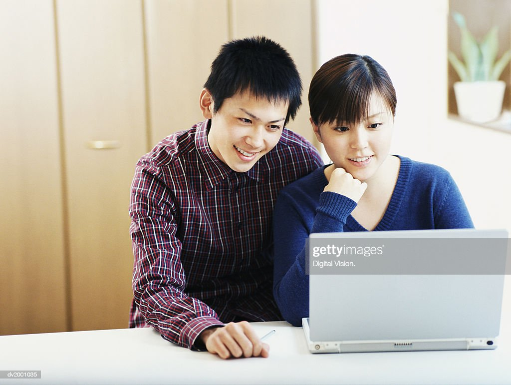 Couple of Students Doing Their Homework on a Laptop : Stock Photo