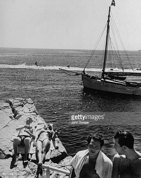 Couple of sunbathers lying on part of Eden Roc, with sail boat in backround.