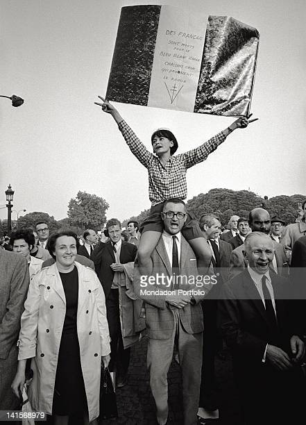 A couple of supporters of Charles de Gaulle shows a three colours flag exalting the right Gaulisme in a demonstration protesting against the general...