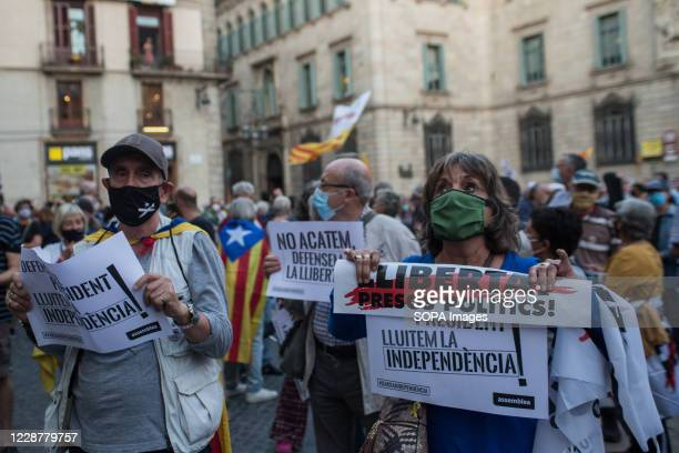 Couple of supporters of the president of Catalonia, Quim Torra, are seen wearing facemasks while displaying banners reading 'freedom, political...