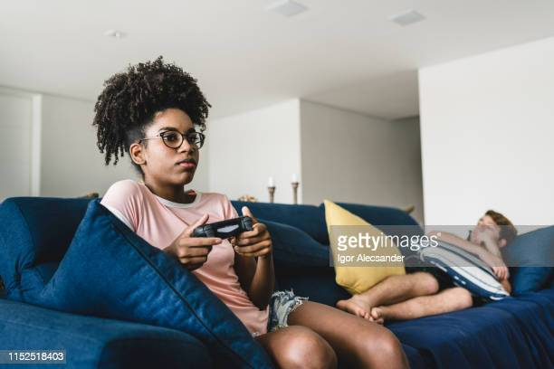 couple of teenage friends at sofa - sentar se imagens e fotografias de stock