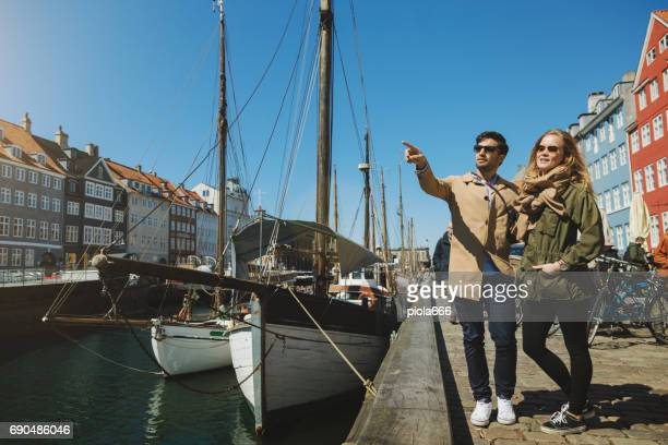 couple of tourist at nyhavn in copenhagen - nyhavn stock pictures, royalty-free photos & images