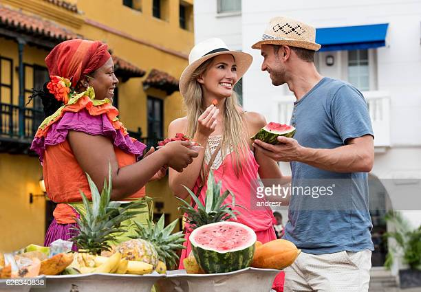 couple of tourist buying fruits in the street - cartagena colombia foto e immagini stock
