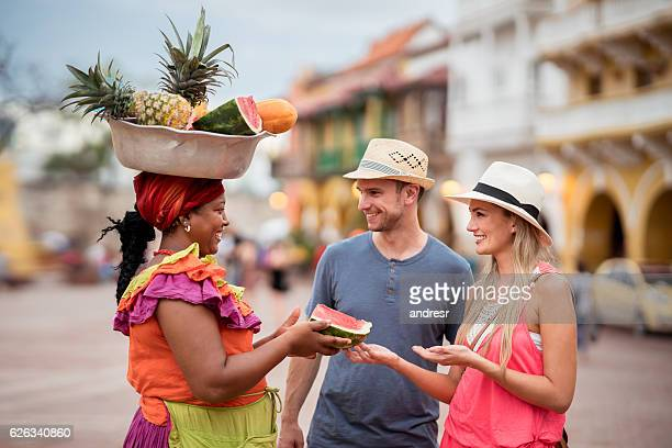 couple of tourist buying fruits in the street - colombia fotografías e imágenes de stock