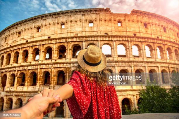 couple of tourist on vacation in front of colosseum rome italy - colosseum stock pictures, royalty-free photos & images