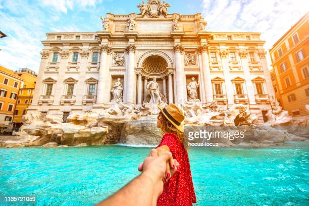 couple of tourist on vacation in front of trevi fountain italy - trevi fountain stock pictures, royalty-free photos & images
