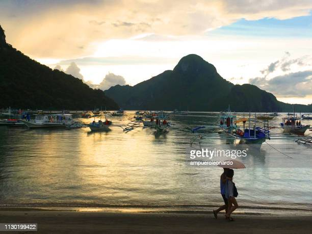 couple of tourist walking in front of the ocean in el nido, philippines - el nido stock pictures, royalty-free photos & images