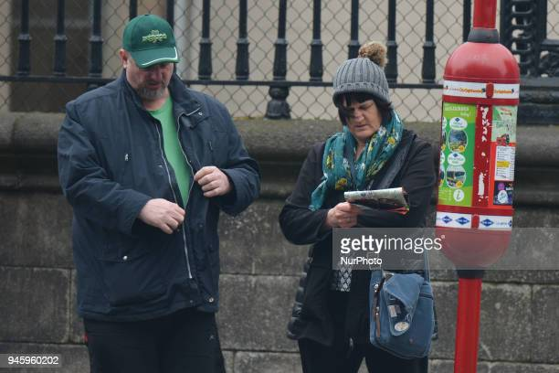 A couple of tourists awaiting for a CitySightseeing Dublin bus On Friday April 13 in Dublin Ireland