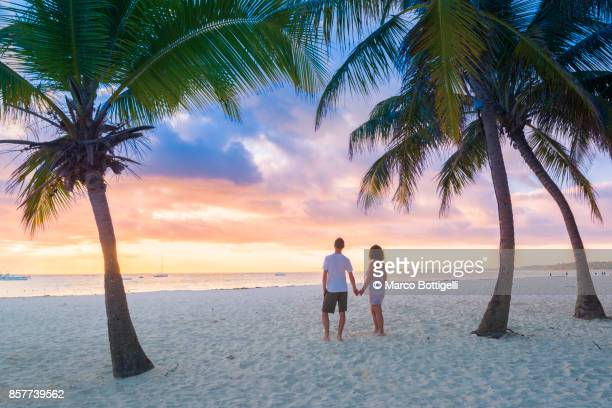 couple of tourists enjoying sunrise on a tropical beach - paisajes de republica dominicana fotografías e imágenes de stock