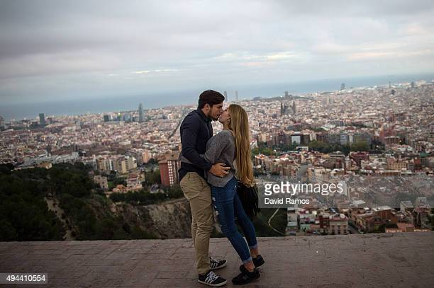 A couple of tourists kiss as they visit a former antiaircraft bunker with the skyline of Barcelona in the background on October 26 2015 in Barcelona...