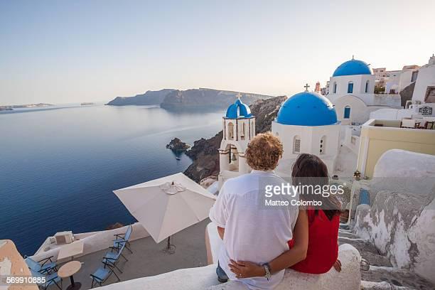 couple of tourists looking at sunset, santorini - griechenland stock-fotos und bilder