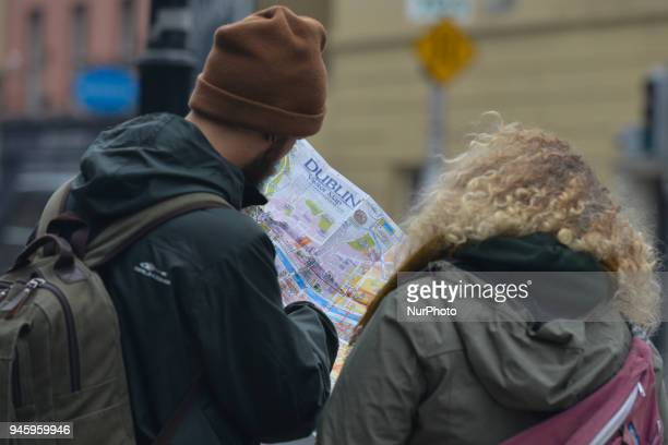 A couple of tourists looks at Dublin map while awaiting for a CitySightseeing Dublin bus On Friday April 13 in Dublin Ireland