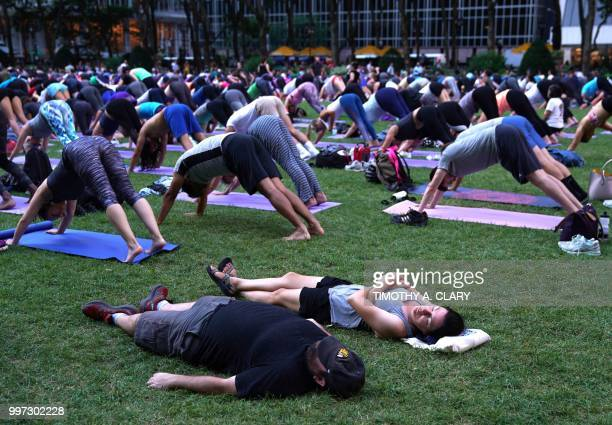 A couple of tourists nap in the grass as people participate in an outdoor yoga event in Bryant Park in New York City July 12 2018