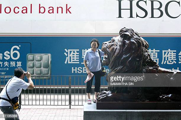 A couple of tourists take photograph next to the lion status which is set in the main entrance of the Hong Kong and Shanghai Bank Cooperation...
