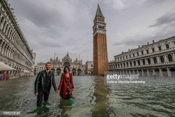 A couple of tourists walk in Piazza San Marco on October 29 2018 in Venice Italy Due to the exceptional level of the acqua alta or High Tide that...