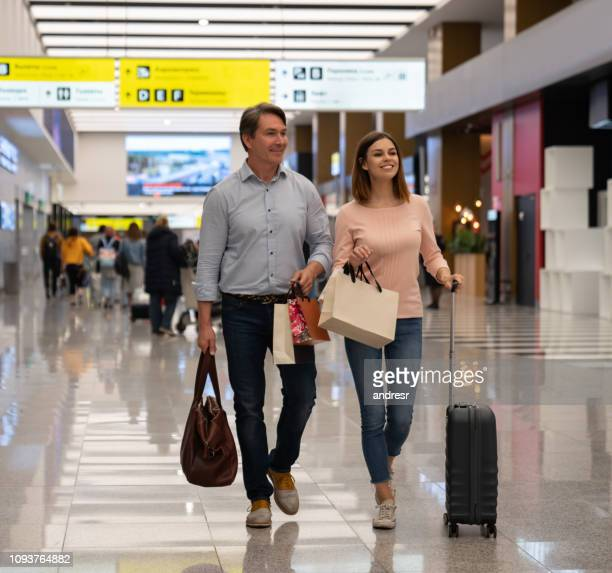 couple of travelers at the airport shopping at the duty free - duty free stock pictures, royalty-free photos & images