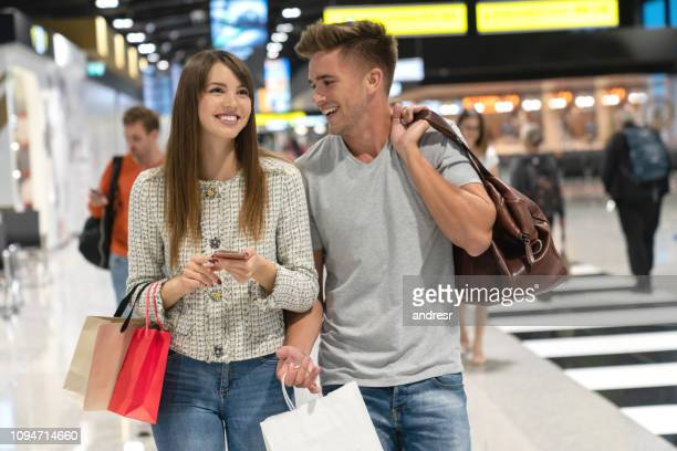 Couple of travelers at the airport shopping at the duty free