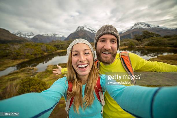 Couple of travellers take selfie in mountain scenery