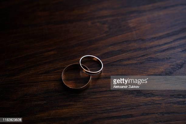 couple of wedding rings on wooden table - trouwceremonie stockfoto's en -beelden