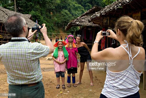 A couple of Western tourists takes a picture of their two daughters with a 'long neck' woman in Nai Soi village Northern Thailand The 'long necks'...