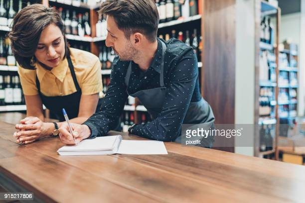 couple of winery owners talking and writing in a textbook - liquor store stock pictures, royalty-free photos & images