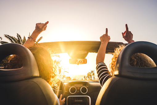Couple of woman friends traveling and driving having a lot of fun dancing in the car with opened roof and summer vacation sunset ocean in front - concept of friendship together and nice lifestyle for independent girls 1137917684