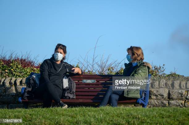 Couple of women wearing protective face masks chat on a park bench at Southsea on the first day of a new national lockdown on November 05, 2020 in...