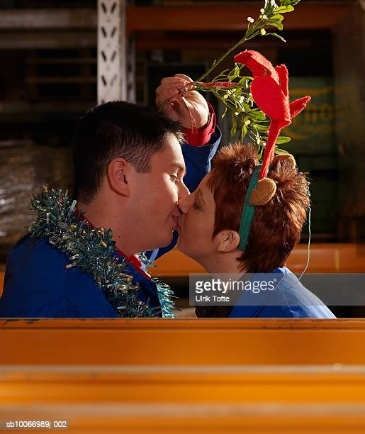 Couple of workers holding mistletoe above heads kissing in warehouse aisle, side view