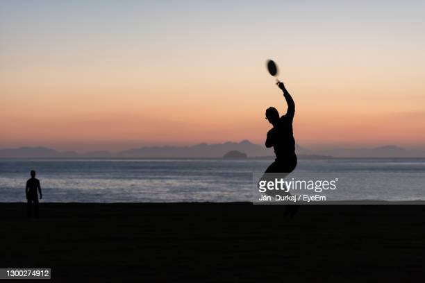 a couple of young adults playing frisbee at dusk - aktiver lebensstil stock-fotos und bilder