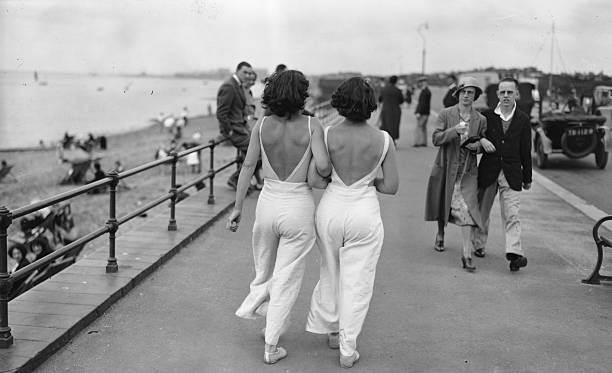 A couple of young bare-backed women strolling along...