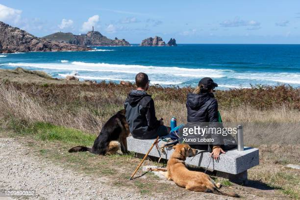 Couple of young hikers rest with their dogs and contemplate the lighthouse of Cape Vilan, in the region of Costa da Morte, seen on August 30, 2020 in...