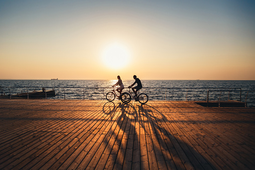 Couple of young hipsters cycling together at the beach at sunrise sky at wooden deck summer time 961581496