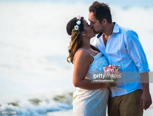 couple of young newlyweds in love on the beach on sunny day - casal jovem stock pictures, royalty-free photos & images