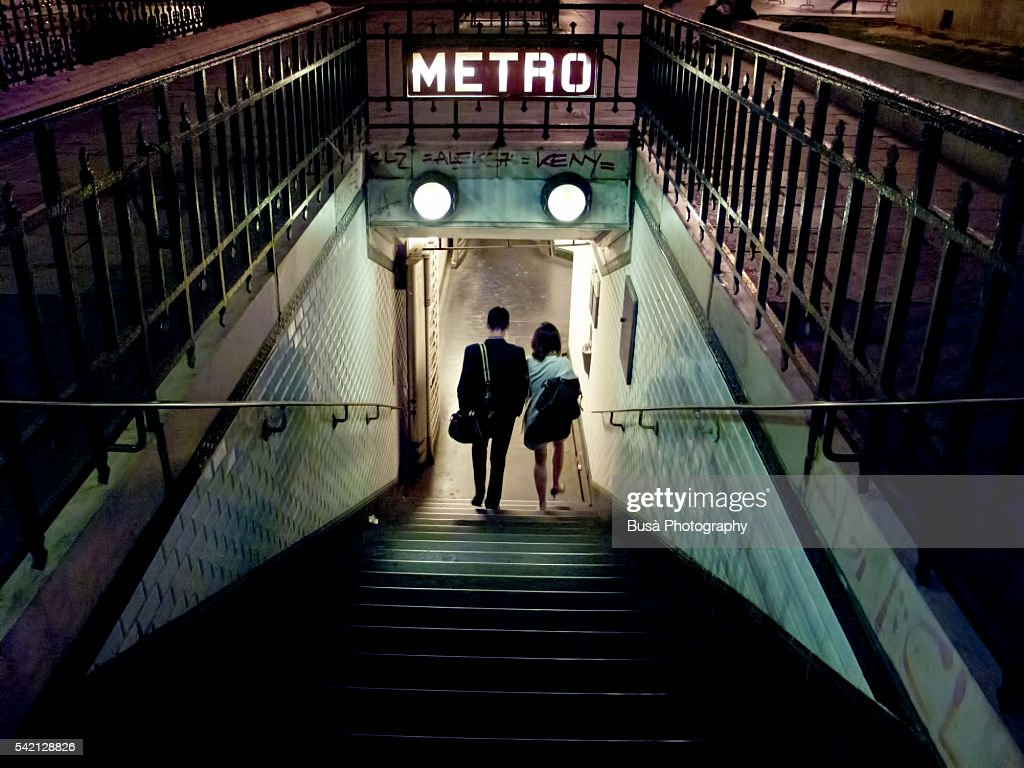 Couple of young people entering a station of the Paris Metro at night. Paris, France : Stock Photo