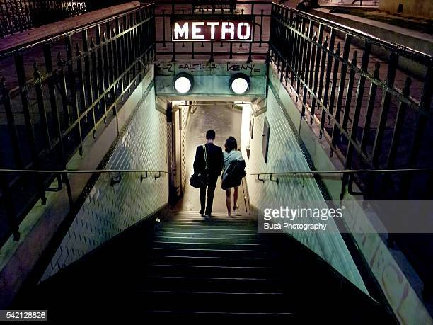 couple of young people entering a station of the paris metro at night. paris, france - underground sign stock pictures, royalty-free photos & images