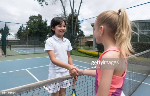 couple of young tennis players handshaking at the court - fair play sport foto e immagini stock