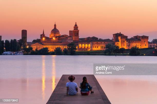 couple of young tourists admiring the view over the historic center of mantua and the mincio river. italy - mantua stock pictures, royalty-free photos & images
