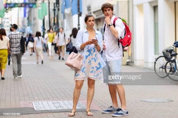 新しい街を探索若い旅行者のカップル。 - 観光客 ストックフォトと画像