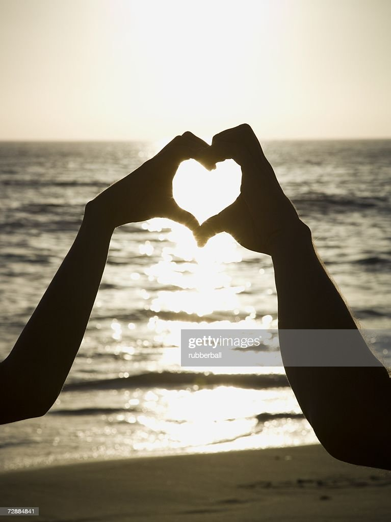 Couple On A Beach Making A Heart Symbol With Their Hands Stock Photo